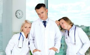 Three clinicians in white coats tired after working week